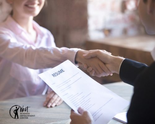 Woman and man shake hands, viewing resume