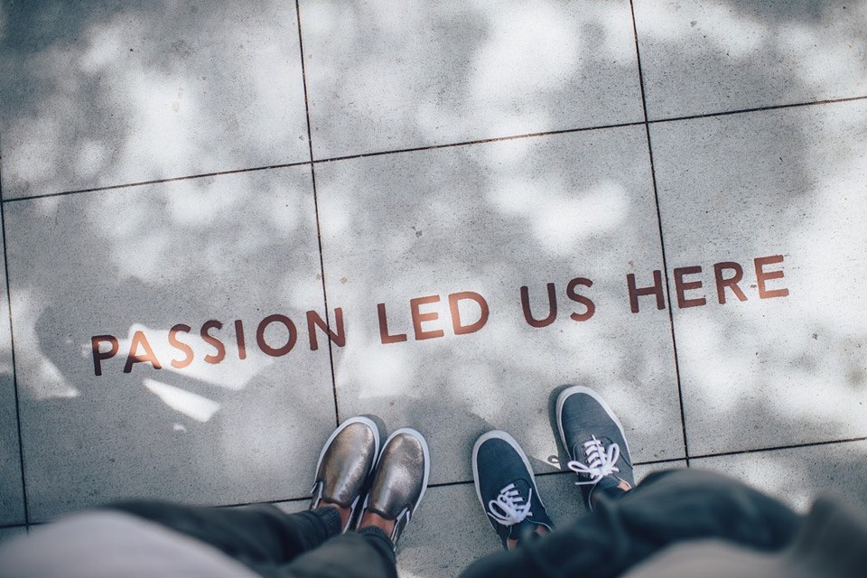 "Image: Feet next to sign ""Passion led us here"" - Coast Women in Business"