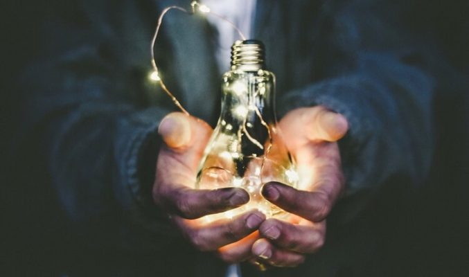 Business lightbulb in cupped hands