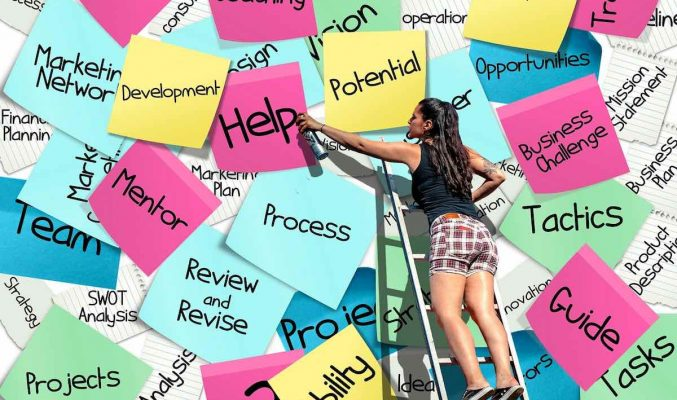 Image: woman on ladder with task-oriented sticky notes - Coast Women in Business