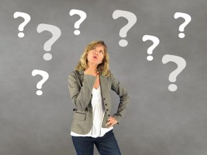 Image: woman pondering decisions, surrounded by question marks